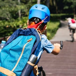 A boy rides on a bicycle with helmet and backpack.